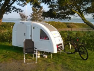 Grey nomads tow caravan with a bike